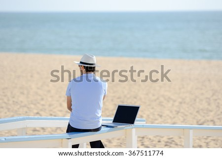 Businessman working with laptop computer on the beach background. Back view of male in hat - stock photo
