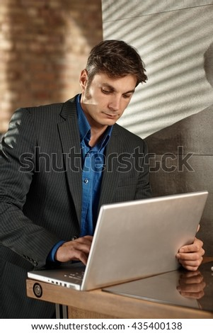 Businessman working with laptop computer, standing at table. - stock photo