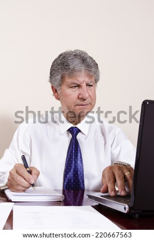 Businessman working with laptop in a interior office.