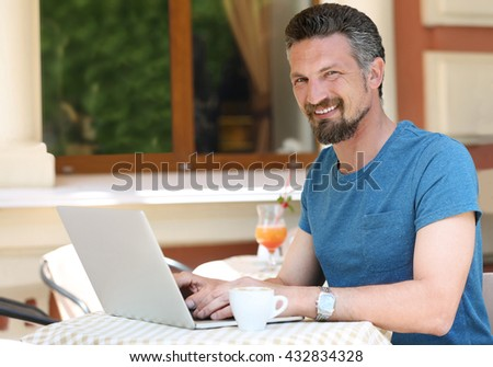 Businessman working with laptop in cafe - stock photo