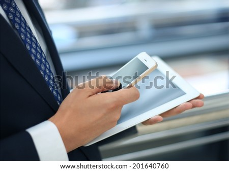 businessman working with modern devices, digital tablet computer and mobile phone - stock photo