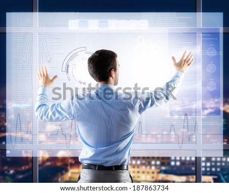businessman working with modern virtual technologies, stands back, hands touching the screen - stock photo