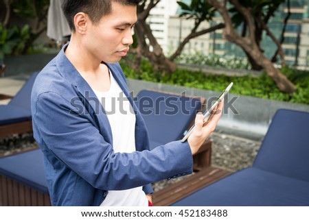 Businessman working with tablet at swimming pool.