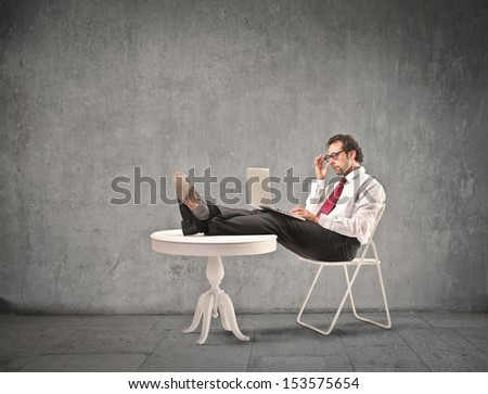 businessman working with tablet comfortable sitting with feet on the table