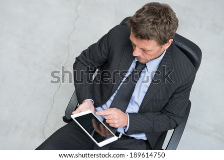 Businessman working with tablet on concrete floor background.