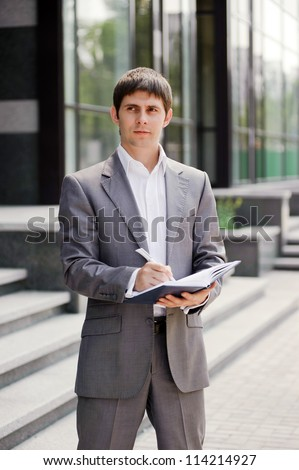 Businessman writes ideas in a notebook