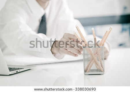 businessman writes in a notebook while sitting at a desk - stock photo