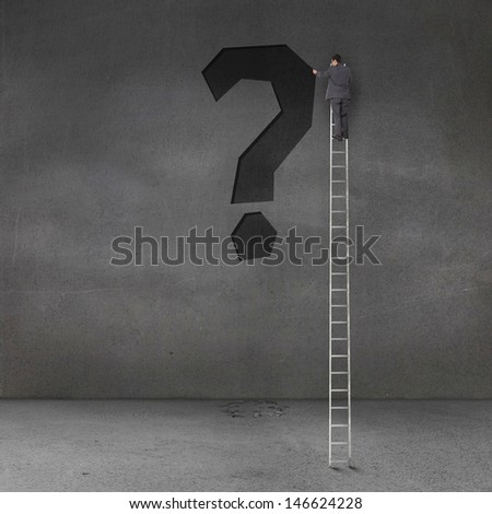 Businessman writing a black question mark on a grey wall - stock photo