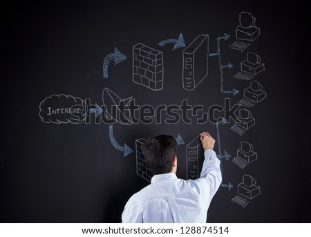 Businessman writing a firewall diagram in a chalkboard - stock photo