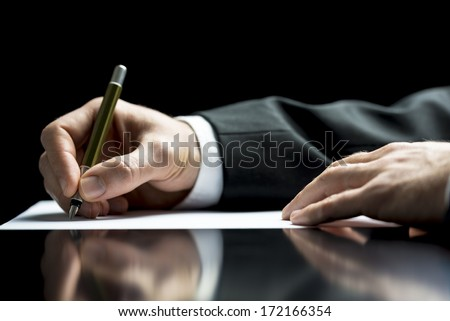 Businessman writing a letter, notes or correspondence or signing a document or agreement, close up view of his hand and the paper - stock photo