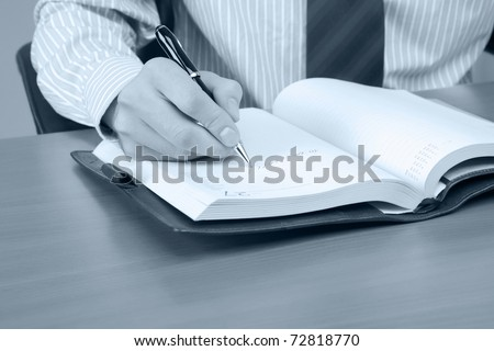 Businessman writing a note at his workplace.