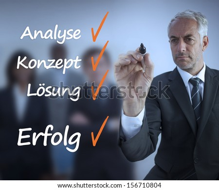 Businessman writing a success checklist in german in front of business team - stock photo
