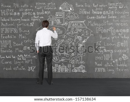 Businessman writing about home sales on a wall 2