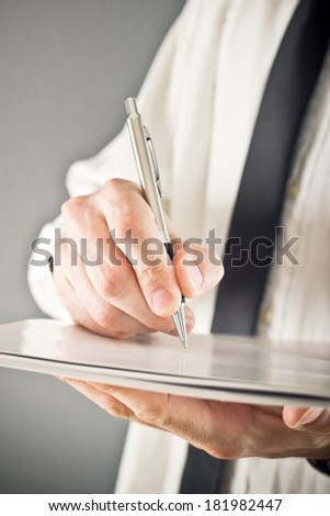 Businessman writing analytic notes or signing document. Close up image with selective focus. Business situation.