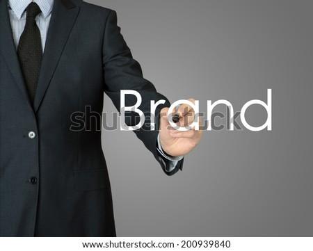 businessman writing brand on grey background - stock photo