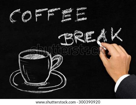 Businessman writing 'coffee break' on blackboard with drawing of cup of coffee - stock photo