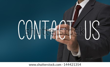 Businessman writing contact us against blue background - stock photo