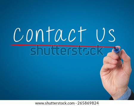 Businessman writing contact us against blue background. Stock Image - stock photo