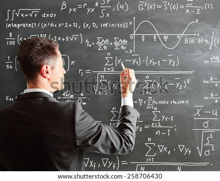 businessman writing formula on chalk board