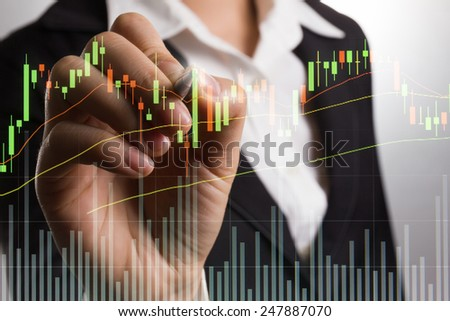 Businessman writing graph for trade stock market on the screen. - stock photo