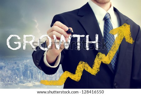 Businessman writing growth with rising arrows above the city - stock photo
