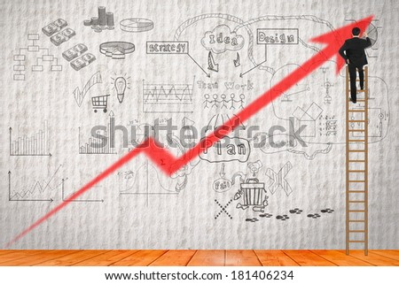 Businessman writing his strategy for buiding business on the old wall - stock photo