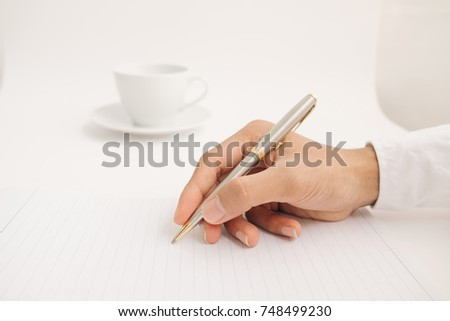Businessman writing in a document, Focused on a hand with pen.