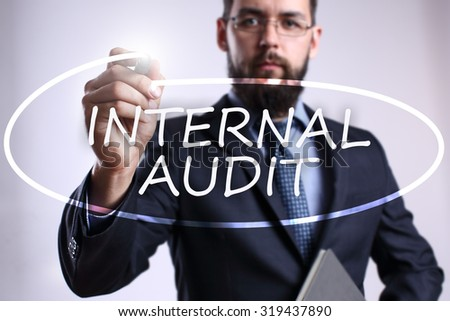 """Businessman writing """"Internal audit"""" with marker on transparent board. Business, internet, technology concept. - stock photo"""