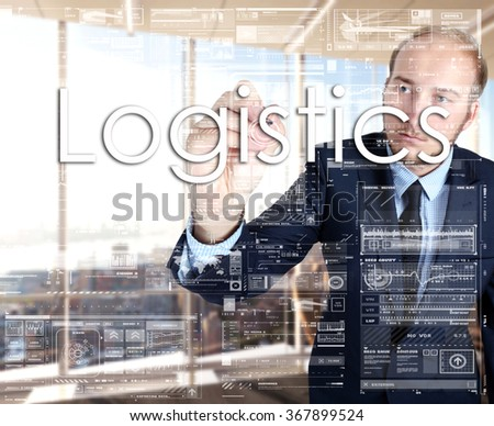 Businessman writing Logistics on virtual screen behind the back of the businessman one can see the city behind the window - stock photo