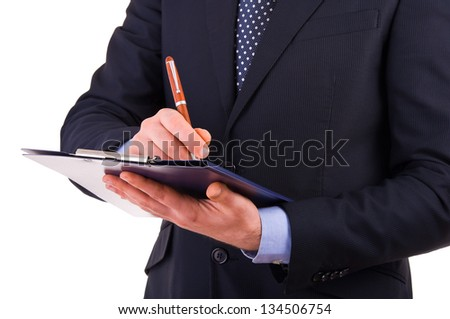 Businessman writing notes on clipboard.