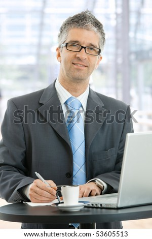 Businessman writing notes on paper standing at coffee table in lobby of corporate building, in front of windows.