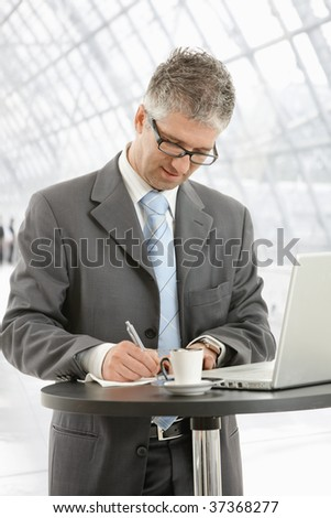 Businessman writing notes on paper standing at coffee table in office lobby.