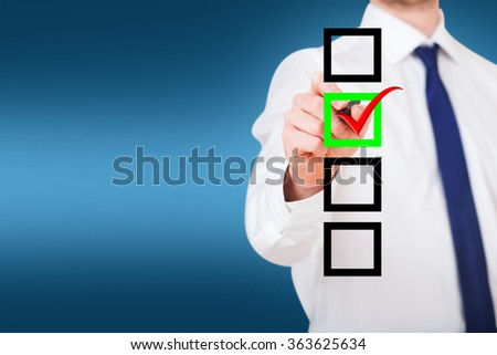 businessman writing on a check box over blue background