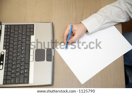 Businessman writing on a sheet of paper near laptop - stock photo