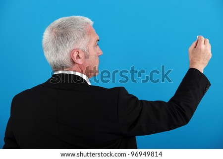 Businessman writing on an invisible board - stock photo