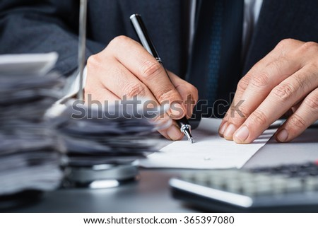 Businessman writing on bill with pile of bills in paper nail - stock photo