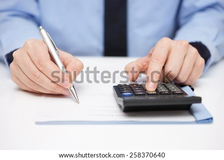 Businessman writing on document and using calculator at the same time - stock photo