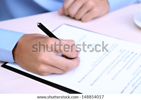 Businessman writing on document in office close-up