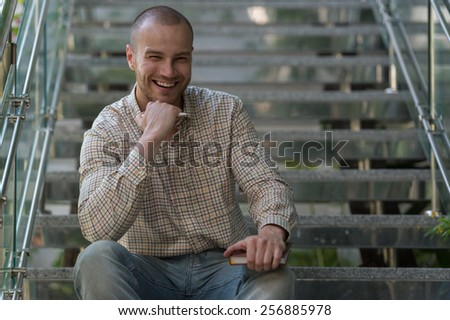 Businessman writing on notebook and planning his day sitting on stairs at office building - stock photo