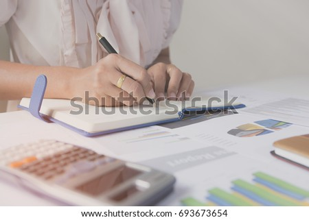 Businessman writing on notebook on wooden table, Concept finance planing and analyzes management.
