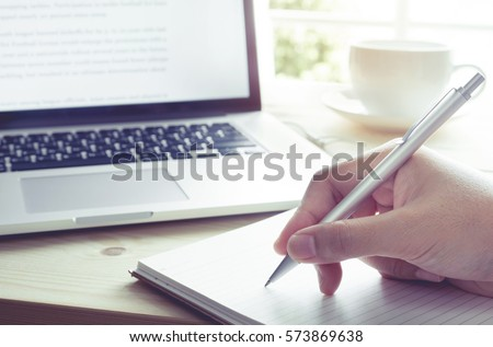 Businessman writing on notebook with laptop.Inspiration moment,working or coffee break in morning