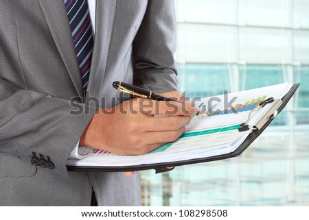 businessman writing on paper in the office - stock photo