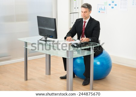 Businessman Writing On Paper Sitting On Pilates Ball In Office - stock photo