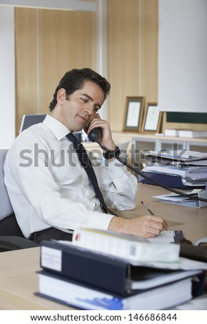 Businessman writing on paper while using telephone at desk in office