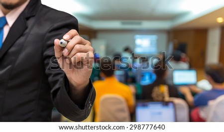 Businessman writing on the Abstract blurred photo of conference hall or seminar room with attendee background - stock photo