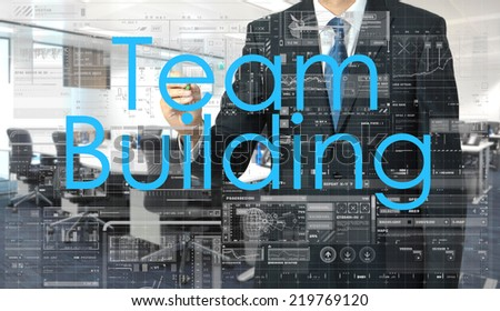 businessman writing on transparent board Team Building with office in background - stock photo
