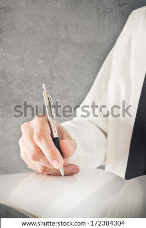 Businessman writing or signing project documentation. Close up image with selective focus. Business situation.