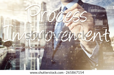 businessman writing Process Improvement on transparent board with city in background - stock photo