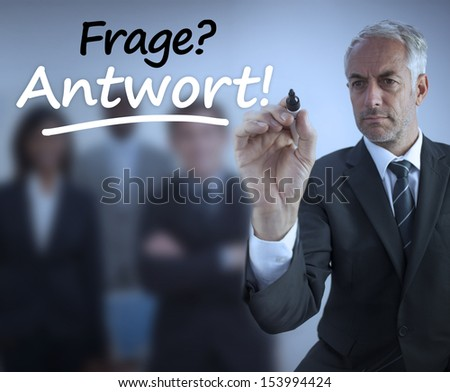 Businessman writing question and answer in german in front of business team - stock photo