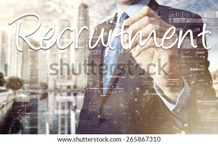 Businessman writing Recruitment on virtual screen behind the back of the businessman one can see the city behind the window - stock photo